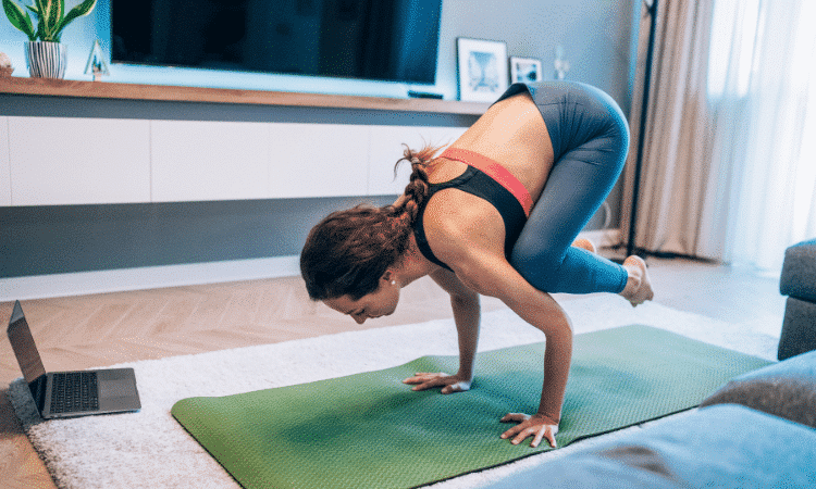 women in crow pose in their home practice