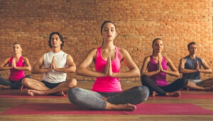Beautiful sports people are sitting in lotus position while doing yoga in modern fitness hall