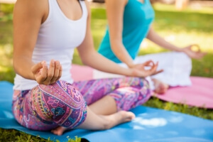 Closeup of a couple of women meditating and doing yoga at a park