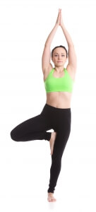 Sporty girl on white background doing exercise for spine, standing in asana Vrikshasana (Vriksasana, Tree Pose), hands above the head in anjali mudra, yoga for relieving stress