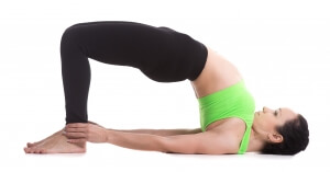 Beautiful sporty girl doing yoga workout, standing in bridge pose, dvi pada pithasana, setu bandhasana, set exercises for strengthening back and shoulders muscles