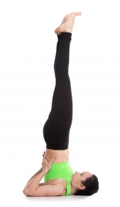 Beautiful sporty girl doing yoga exercises for abs strength, Supported Shoulderstand asana, Salamba Sarvangasana